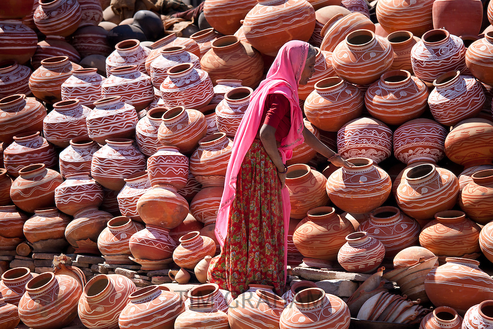Indian woman selling clay water pots in old town Udaipur, Rajasthan, Western India,
