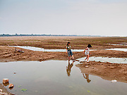 05 ARPIL 2010 - NAKHON PHANOM, THAILAND: Sisters play in the empty Mekong River near Nakhon Phanom, Thailand. Normally the river flows through the entire river bed, but it's currently running through a channel in the bottom of the river bed, not visible in the background of the photo. Thais have turned their side of the nearly empty river into a beach and playground. According to people who live here, the river is at its lowest point in nearly 50 years.   PHOTO BY JACK KURTZ
