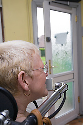 Woman with Cerebral Palsy operating personal environment controls to open her back door,