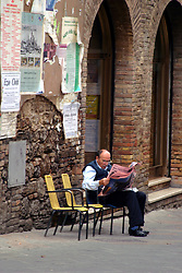 A man reads his morning newspaper along a San Gimignano street.