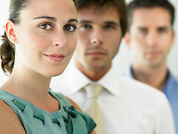 Businesswoman and two businessmen focus on woman portrait