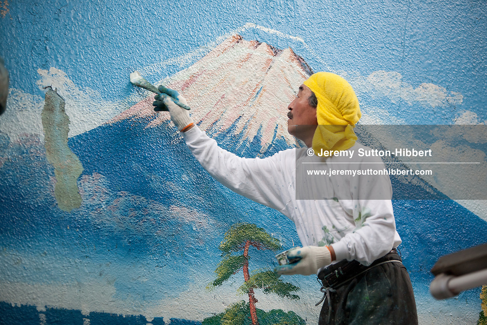 Penki-e (painter who uses paints) Morio Nakajima begins to paint a fresh mural of Mount Fuji over the top of an older similar view by painter Hayakawa Toshimitsu, at the 'Moto No Yu' sento (public bath house) in Shinozaki, in eastern Tokyo, Japan, on Thursday 23rd June 2011. Nakajima-san and Kiyoto Maruyama are the two remaining painters of Mt Fuji murals in the Kanto area of Japan. Nakajima-san currently undertakes approximately 70 such mural assignments a year, and they each cost the sento owners approximately JPY 100,000.  Mizuki Tanaka,  a graduate of art history, has been an apprentice to Nakajima-san for 6 years but has not yet progressed to the level where she is allowed to paint the Mt Fuji itself, at present she paints the other background details of the mural but not the mountain itself.