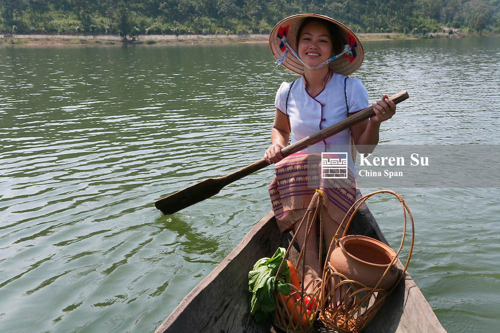 Tribal girl with conical hat on dug-out canoe on Dak Minh Lake.