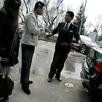 BEIJING, APRIL-22, 2010:   customers talk to a salesperson while they are waiting to get a car plate attached to their newly bought BMW  outside the  BMW dealership .