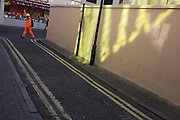 Construction worker and yellow light reflected from an adjacent building on to a wall in London's Soho.