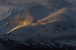 A sliver of an early morning sunrise shines on  the slopes of Mount Jonathan Ward outside Haines, Alaska near the Alaska Chilkat Bald Eagle Preserve.