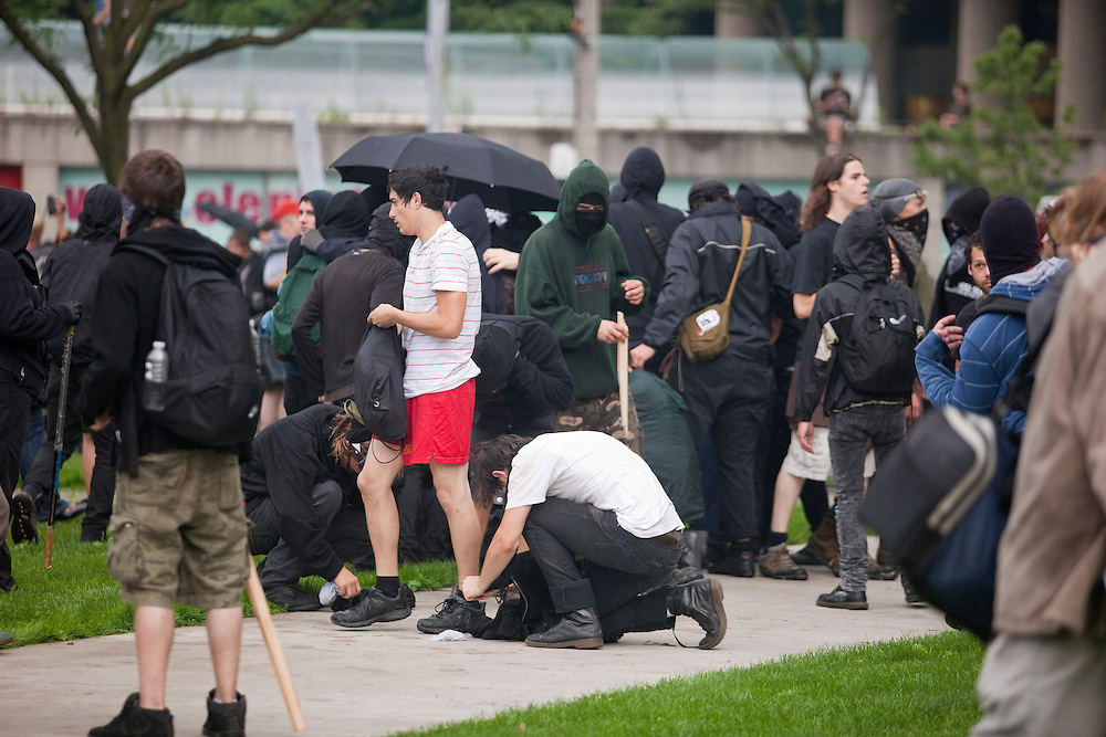 Protesters thought to be part of the anarchist group the black block change from their black outfits into street clothes as police surround their position following their anti g20 rampage through the streets of Toronto, Canada, June 26, 2010.<br /> AFP/GEOFF ROBINS/STR