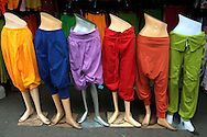 Colorful Pants Display at Chatuchak Market or sometimes called the Weekend Market in Bangkok is the largest market in Thailand, and one of the largest of the world.  It covers over 35 acres and contains more than 5,000 stalls not counting wandering vendors and street entertainers. It is estimated that the market receives between 200,000 and 300,000 visitors each day. The market offers a wide variety of products including household items, clothing, Thai handicrafts, religious artifacts, collectibles, foods and even live animals.