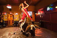 Woman, mechanical bucking bull, riding, Livingston, Montana, MODEL RELEASED
