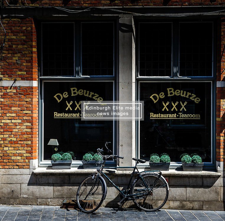 A bicycle parked against a restaurant window in Briges, Belgium.<br /> <br /> (c) Andrew Wilson | Edinburgh Elite media