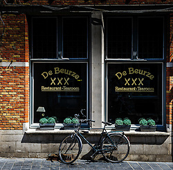 A bicycle parked against a restaurant window in Briges, Belgium.<br /> <br /> (c) Andrew Wilson | Edinburgh Elite media