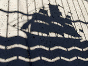 shadow of old wooden ship on pavement