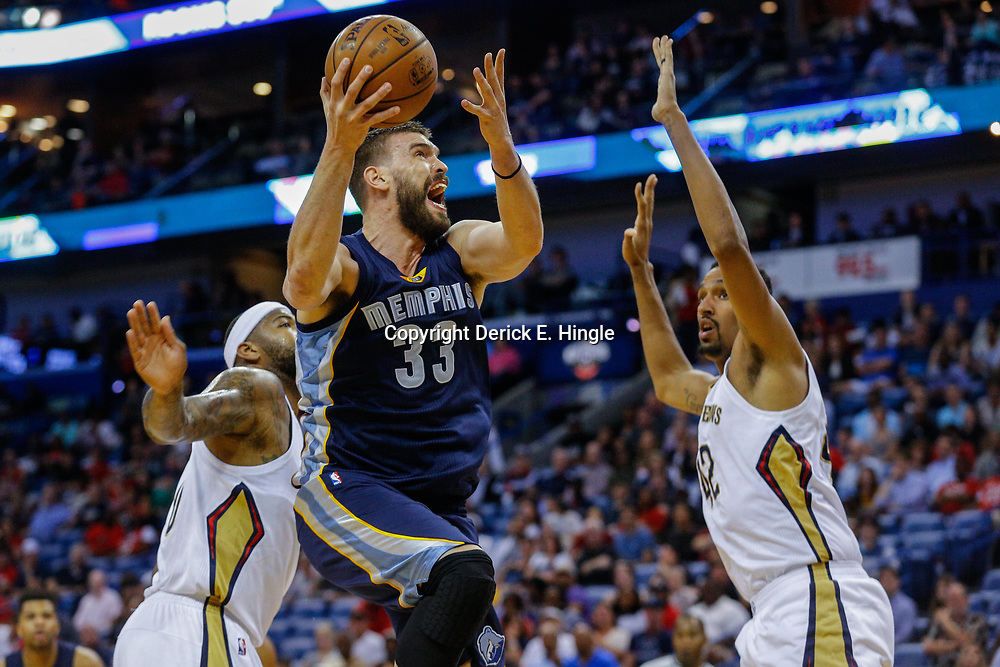 Mar 21, 2017; New Orleans, LA, USA; Memphis Grizzlies center Marc Gasol (33) shoots over New Orleans Pelicans center Alexis Ajinca (42) and forward DeMarcus Cousins (0) during the first quarter of a game at the Smoothie King Center. Mandatory Credit: Derick E. Hingle-USA TODAY Sports