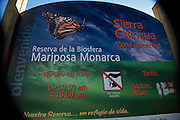 A sign marking the entry into the Monarch Butterfly Biosphere Reserve in Sierra Chincua central Mexico in Michoacan State. Each year hundreds of millions Monarch butterflies mass migrate from the U.S. and Canada to Oyamel fir forests in the volcanic highlands of central Mexico. North American monarchs are the only butterflies that make such a massive journey—up to 3,000 miles (4,828 kilometers).