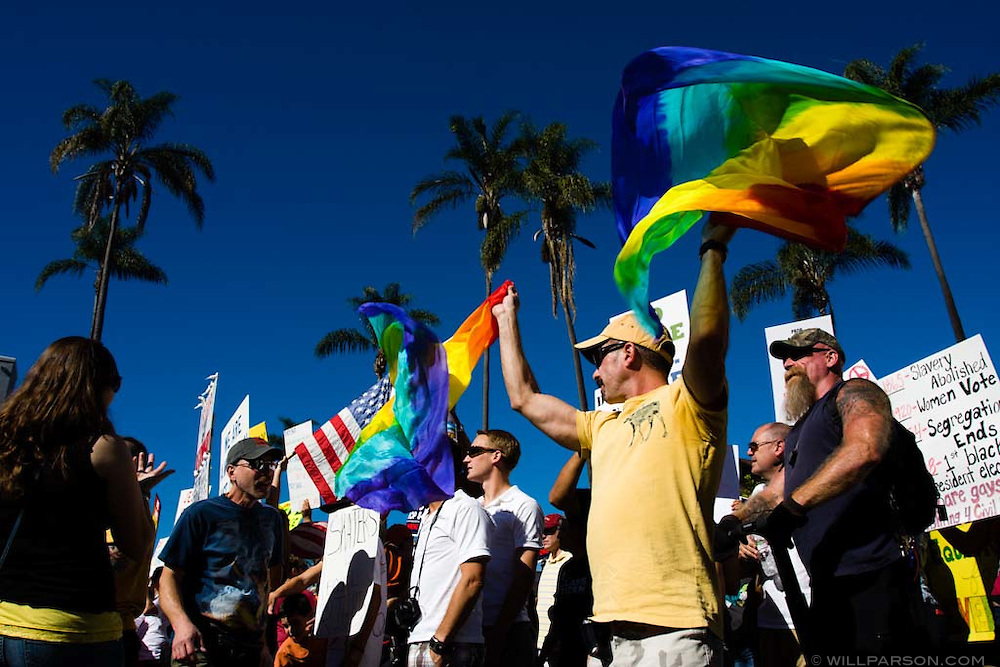 Jerry Tolansky waves two rainbow flags near the front of the procession.  An estimated 20,000 people marched down Sixth Avenue in San Diego on November 15, 2008 to protest the passing of Proposition 8, which banned gay marriage in California.  The overwhelmingly peaceful event was the largest of several protests held nationwide, and culminated in a rally in front of the County Administration Building overlooking San Diego's waterfront.