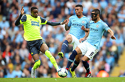 Manchester City's Ilkay Gundogan (right) and Gabriel Jesus battle for the ball with Huddersfield Town's Adama Diakhaby