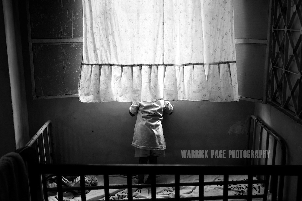 KARACHI, PAKISTAN - MARCH 7: A young orphan girl stands in her cot looking out the window into the street at the Edhi orphanage on March 7, 2008 in Karachi, Pakistan. The Edhi Foundation urges women give up unwanted children rather than abandon or kill in order to cover up children conceived out of wedlock, or through rape. The Edhi Foundation orphanages represent a microcosm of Pakistan's absolute poverty where children are its first casualty, tragedy and hope collide on a daily basis, and life and death are in constant flux existing only rooms apart. Pakistan is a country more than a third of it's population live in absolute poverty. As world attention fixates on Pakistan's ongoing political turmoil, generations of children are being abandoned due to Pakistan's spiraling poverty and growing instability. Some are born out of wedlock - a major social taboo - others discarded due to physical and mental disabilities, but nearly all are abandoned due to poverty. Boys and girls alike are abandoned every year, found in dumpsters mauled by rats and dogs, or left to fend for themselves on the streets of Karachi's sprawling and unforgiving metropolis. The lucky ones find their way to the Edhi Foundation orphanages. . (Photo by Warrick Page)