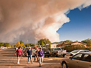 "03 JUNE 2011 - SPRINGERVILLE, AZ: The smoke column off the Wallow fire towers over people going to the community meeting about the fire in Eager Friday night. High winds and temperatures have continued to complicate firefighters' efforts to get the Wallow fire under control. The  mandatory evacuation order for Alpine was extended to Nutrioso, about 10 miles north of Alpine and early Friday morning fire was reported on the south side of Nutrioso. The fire grew to more than 106,000 acres early Friday with zero containment. A ""Type I"" incident command team has been called in to manage the fire.   PHOTO BY JACK KURTZ"