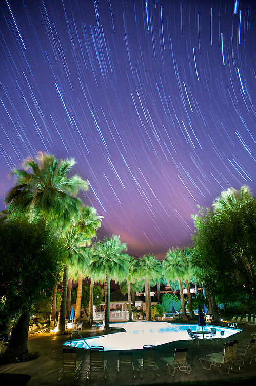 Night shot of pool and palm trees with special effects on the stars in Palm Springs, California