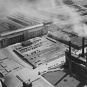 """1926 aerial view of the Studebaker Corporation's """"Plant 2"""".  The Studebaker power plant (smokestacks), building #78 (five story) Machine Shop (sawtooth roof) and foundry (upper right) are visible."""