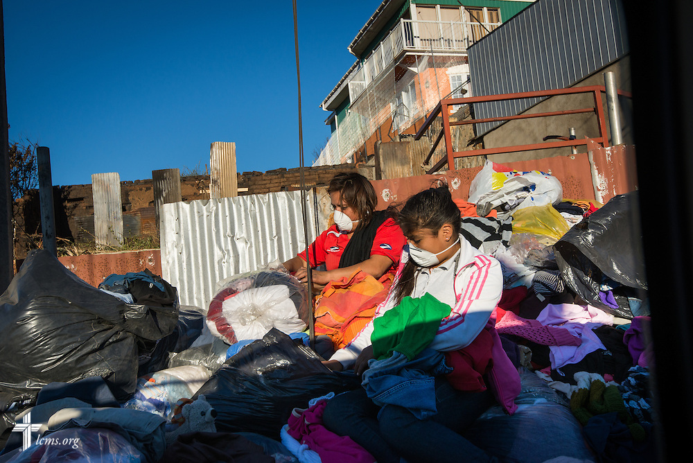 Young women search through bags of clothes on Monday, April 21, 2014, on a narrow pathway alongside a hillside of homes affected by a devastating fire in Valparaíso, Chile. The catastrophic fire that tore through the hillsides above the historic port city fire killed 15 people, destroyed about 3000 homes, and left approximately 15,000 people homeless.  LCMS Communications/Erik M. Lunsford