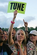 A girl holding up a 'Tune' sign in the crowd, O2 Wireless festival, Hyde Park 2007