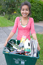 Teenage girl carrying curb side recycling collection box out onto the pavement ready for collection,