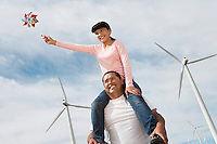 Girl (7-9) sitting on fathers shoulders at wind farm