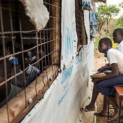 Students of Valley View secondary school at the Bidi Bidi refugee settlement listen to their class through a window because their classroom is full. The classroom has an ideal capacity of 80 students but currently 150 attend. This school has 15 teachers for 1,888 students.