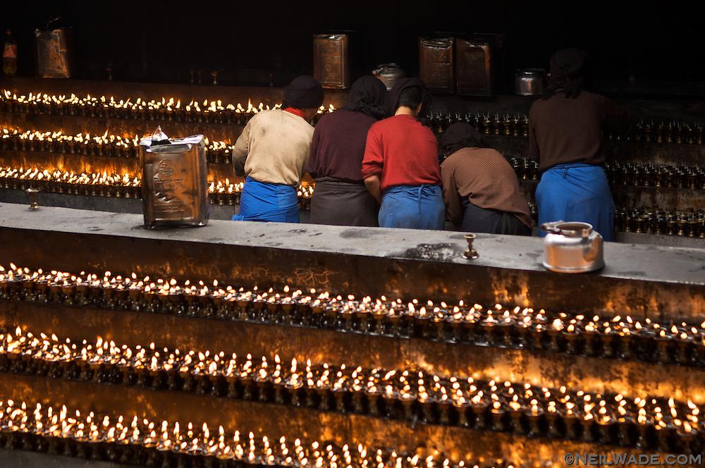 Tibetan nuns light hundreds of prayer candles at The Jokang, Tibetan Buddhism's most holy temple.  Lhasa, Tibet.