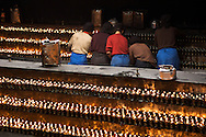 Tibetan nuns light hundreds of prayer candles at The Jokang, Tibetan Buddhism's most holy temple.  Lhasa, Tibet.