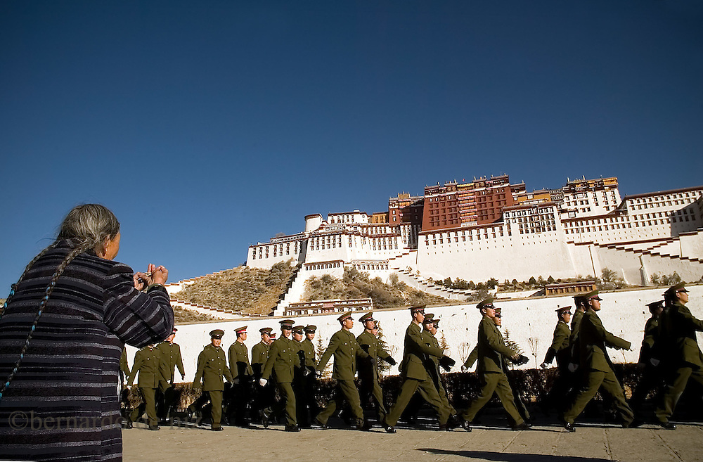 A chinese soldiers march between the Potala palace and old Pilgrim pray during the celebration of Tibetan New Year, in Lasa..The Potala Palace was once the seat of the Tibetan government and the winter residence o f the Dalai Lamas. Lasa,Tibet, China/Feb. 22, 2007.