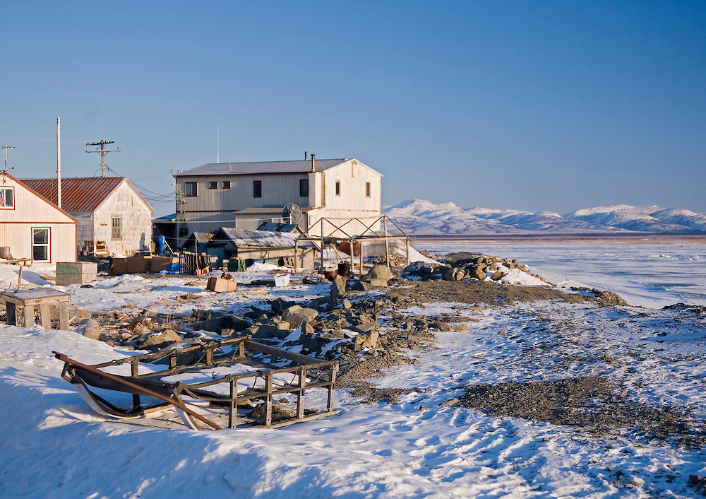 Alaska. Dog mushing sled rests in front of a typical Unalakleet home, with the Nulato Hill visible in the background.
