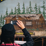 Heather Goodrich takes an iphone photo of the Gwin Lodge sign in Cooper Landing, Alaska.