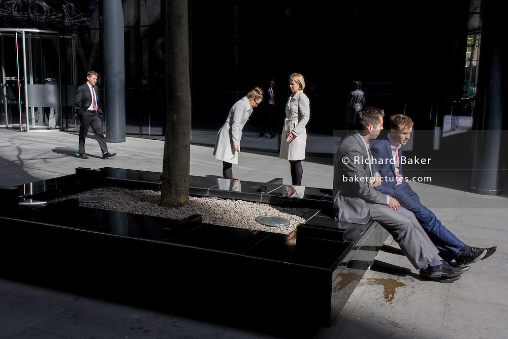 Smoking women and dejected-looking businessmen sit looking at the ground in sunshine outside an office complex in the City of London.