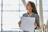 Portrait of businesswoman standing while holding blank white board in arrival area at airport
