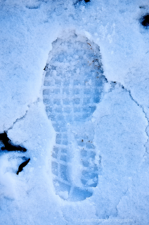 A single footprint made by a large boot disturbs the freshly fallen snow on a bright winters day.