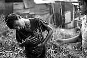 Obed plays in the pouring rain with his neighbors.