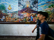 21 JANUARY 2018 - LEGAZPI, ALBAY, PHILIPPINES:  People at Our Lady of the Gate Parish (Parroquia Nuestra Señora de la Porteria) walk past a painting of the Mayon eruption in 1814. The Mayon volcano continued to release smoke and ash Sunday morning. Mayon is the most active volcano in the Philippines. More than 30,000 people have been evacuated from communities on the near the Mayon volcano in Albay province in the Philippines. Most of the evacuees are staying at schools in communities outside of the evacuation zone.   PHOTO BY JACK KURTZ