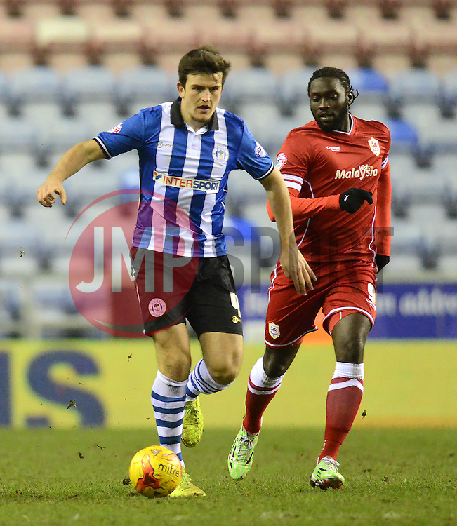Wigan Athletic's Harry Maguire competes with Cardiff City's Kenwyne Jones - Photo mandatory by-line: Richard Martin-Roberts/JMP - Mobile: 07966 386802 - 24/02/2015 - SPORT - Football - Wigan - DW Stadium - Wigan Athletic v Cardiff City - Sky Bet Championship