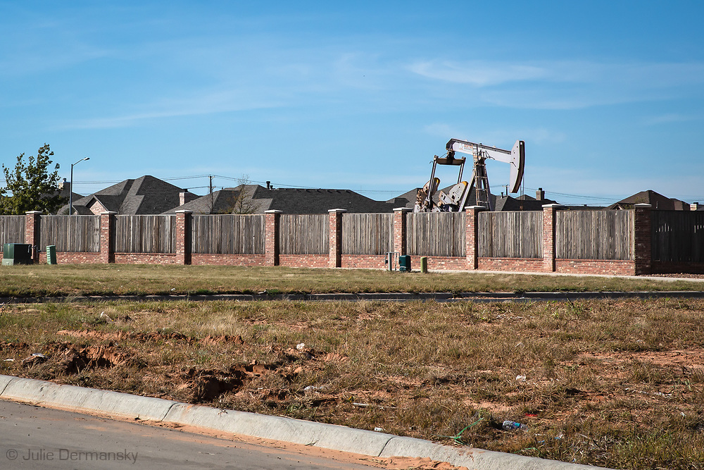 Pump jack in Midland, Texas near homes in the Permian Basin.