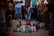 "Farmers from Toconce, a village that has partly sold their water, pray before an offering to Pachamama (mother earth) during the yearly ""canals cleansing"" festival, where men shovel the mud from canals that bring the water to their farms. But these days the work is mostly symbolic, since due to scarcity of water and the improvement of the canals there is almost no mud to shovel. But the festival is one of the few instances when the villagers meet again to revive their tradition, most of them have moved to live in the cities. Atacama desert, Chile. October 2009."