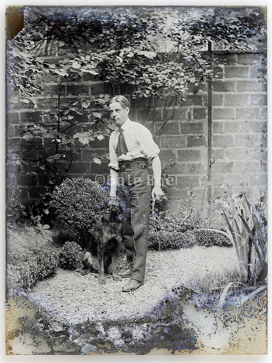 young adult man with dog in backyard garden eroding glass plate early 1900s France Paris