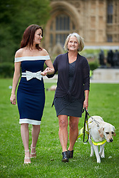 © Licensed to London News Pictures. 25/05/2016. LONDON, UK.  Photocall organised by Guide Dogs for the Blind. The charity is highlighting the daily difficulties faced by guide dogs users including taxis and businesses refusing to allow the animals inside. in this picture: Reality TV star JESS IMPIAZZI with her blind mother DEBBIE IMPIAZZI and six year old guide dog Kacey.  Photo credit: Cliff Hide/LNP