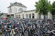 Voor het station in Leeuwarden staat de fietsenstalling vol met fietsen.<br /> <br /> At the train station of Leeuwarden, the bike parking is full with bicycles.