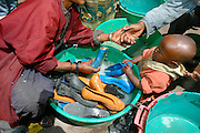 "ADDIS ABABA, ETHIOPIA..The ""Mercato"", biggest market between Cairo and Cape Town. Little kid washing Shoes..(Photo by Heimo Aga)"