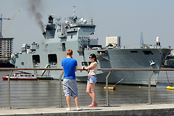 © Licensed to London News Pictures. 25/07/2012. London, UK .  A couple take a picture of HMS Ocean moored in the Thames for the Olympic games 2012 in the sunshine as temperatures reach 30 degrees at Greenwhich Pier in London today 25 July 2012. Photo credit : Stephen Simpson/LNP