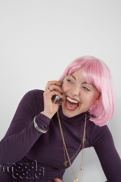 Young woman wearing pink wig laughing into mobile phone