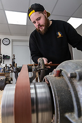 Umbrella maker Lee carefully cuts a shaft to the correct length. Craftspeople at Fox Umbrellas Ltd, a company in Croydon, Surrey, that has been going for over 150 years hand build quality umbrellas. Croydon, Surrey, March 06 2019.