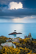 A dramatic storm cloud passes over Noirmont Point lighthouse. Noirmont Point itself is the site of a German Second World War Command Bunker. Jersey, Channel Islands.